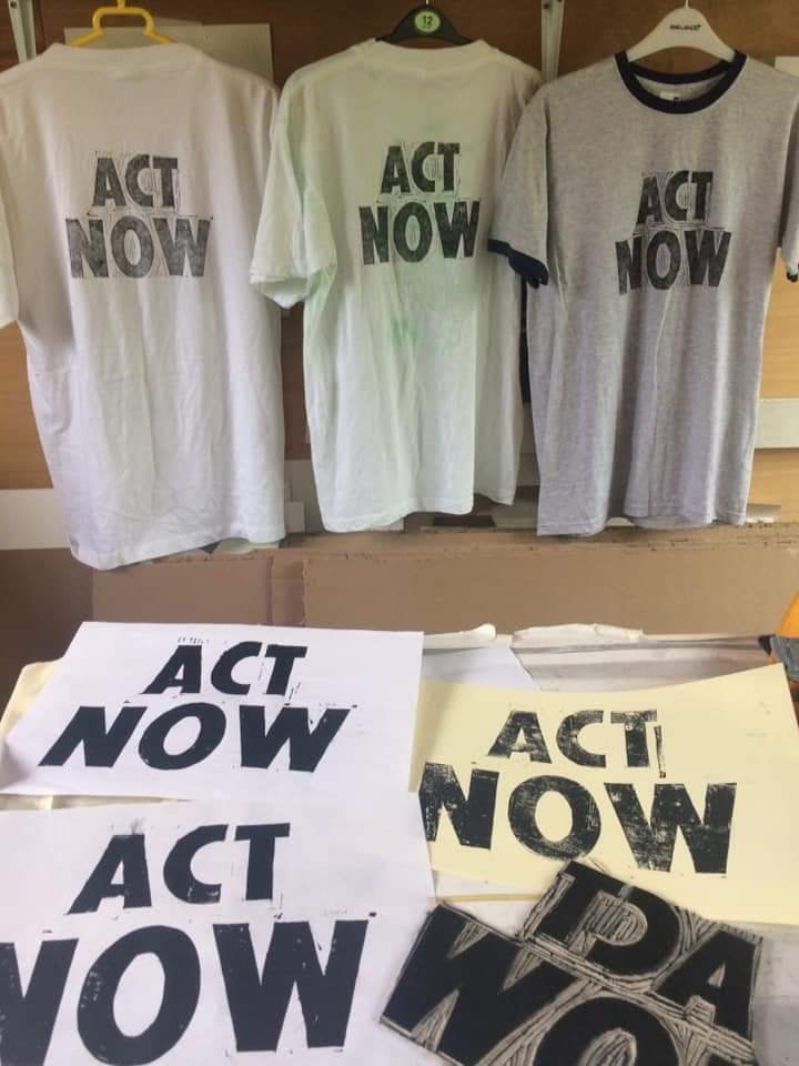 Three t shirts hang with act now written on them, papers and a blaock stamp in the foreground.