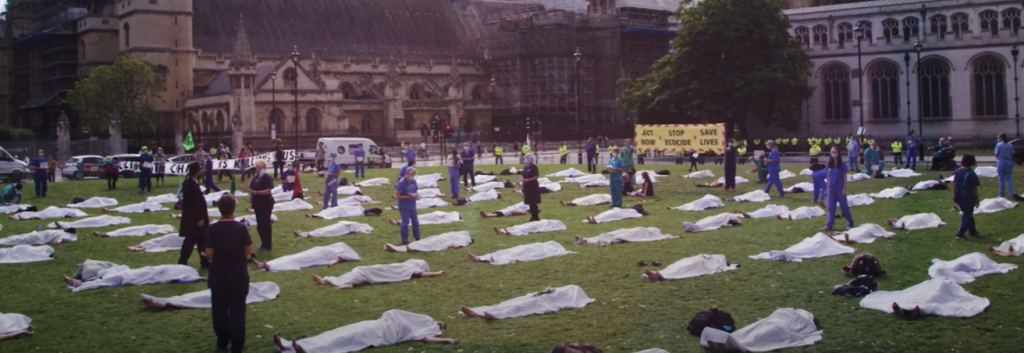 Lots of people pretending to be corpses lie under white sheets on Parliament green