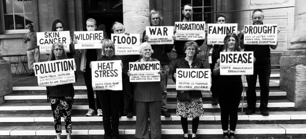12 rebels stand outside the sub rooms holding signs explaining reasons people could die during the climate emergency.